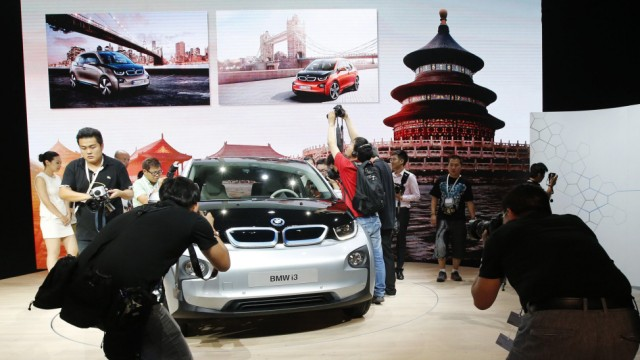 Journalists take pictures of BMW's first all-electric car, i3, at its unveiling ceremony in Beijing