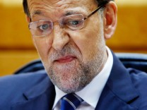 Spanish Prime Minister Mariano Rajoy reacts after drinking a glass of water as Spanish opposition leader Rubalcaba speaks during a session at Madrid's Senate