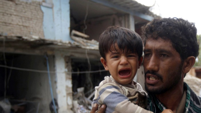 Afghan policeman carries a child at the site of a suicide attack at the Indian consulate in Jalalabad