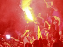 Anti-government protesters hold flares and shout slogans during a demonstration in Tunis
