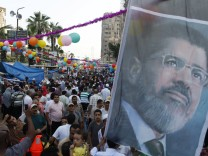 Members of the Muslim Brotherhood and supporters of deposed Egyptian President Mursi walk with their families in the sit-in area of Rab'a al- Adawiya Square