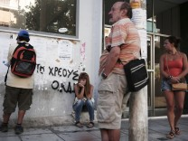 People wait outside a Greek Manpower Employment Organisation office at Kalithea suburb in Athens