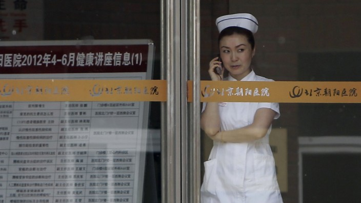 A hospital staff member uses her mobile phone inside the Chaoyang Hospital, where Chinese activist Chen was reported to be staying at, in Beijing