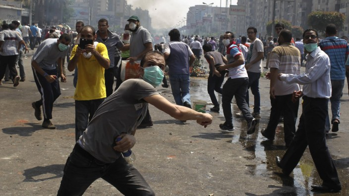 Members of the Muslim Brotherhood and supporters of ousted Egyptian President Mohamed Mursi throw stones at riot police and army personnel during clashes in Cairo