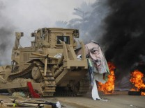 A poster of deposed Egyptian President Mohamed Mursi lies on a bulldozer near Cairo University and Nahdet Misr Square in Giza, south of Cairo