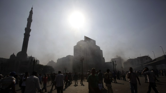 Smoke rises over Ramses Square as members of the Muslim Brotherhood and supporters of ousted Egyptian President Mohamed Mursi protest in front of Azbkya police station in Cairo