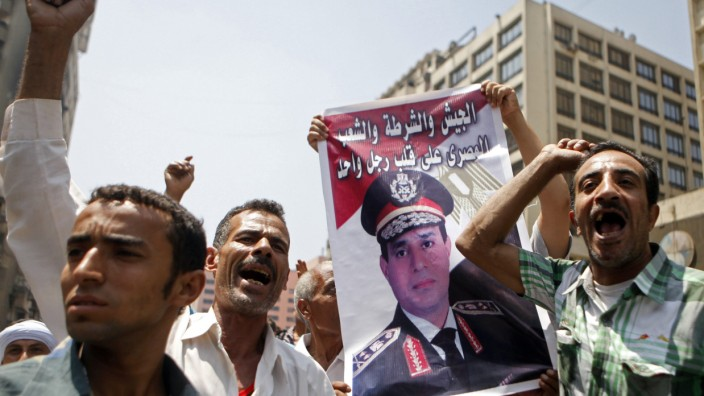 Supporters of the interim government installed by the army cheer Egypt's army chief General Abdel al-Sisi and shout slogans against the Muslim Brotherhood in front of al-Fath mosque in Cairo