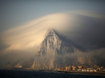 Cloud partially covers Rock of the British territory of Gibraltar at sunrise before Spanish fishermen take part in a protest in Algeciras bay