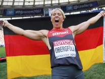 Obergfoll of Germany celebrates with her national flag after winning the women's javelin throw final during the IAAF World Athletics Championships at the Luzhniki stadium in Moscow