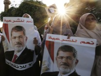 Supporters of deposed Egyptian President Mohamed Mursi hold up posters of him during a protest along Zahara street in Cairo