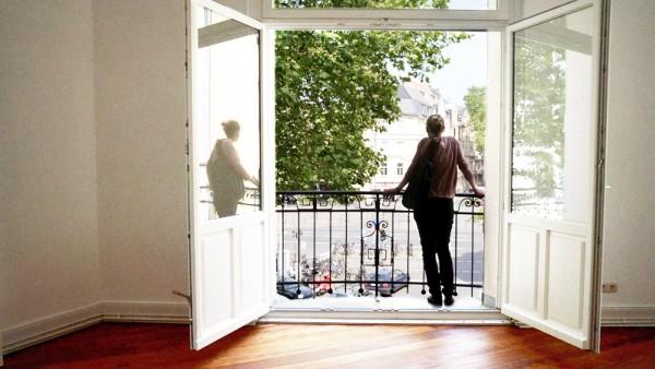 Frau bei wohnungsbesichtigung mieten stadt wohnung appartment parkett altbau einziehen umziehen ausziehen fenster balkon ausblick kaufen miete