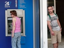 People make transactions at ATM machines outside a bank branch in Athens