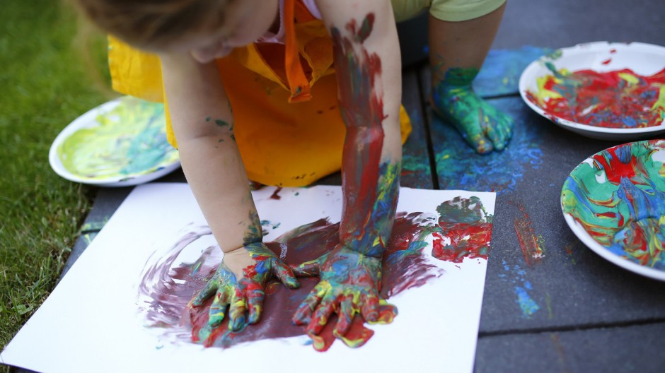 Two year-old Kaethe plays with paints in the garden of her home in Hanau