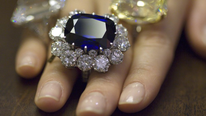 A Christie's employee wears a sapphire  and diamond ring, a 30.52 carat diamond ring and a Fancy Intense Yellow diamond ring during an auction preview in Geneva