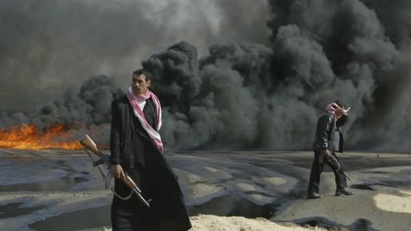 File photo of Iraqi policemen guarding the burning pipeline near the city of Kerbala