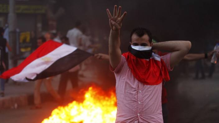 A supporter of Mursi makes the 'Rabaa' or 'Four' gesture during clashes at Mohandiseen in Cairo
