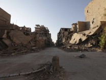 A view of a damaged street and buildings in Deir al-Zor