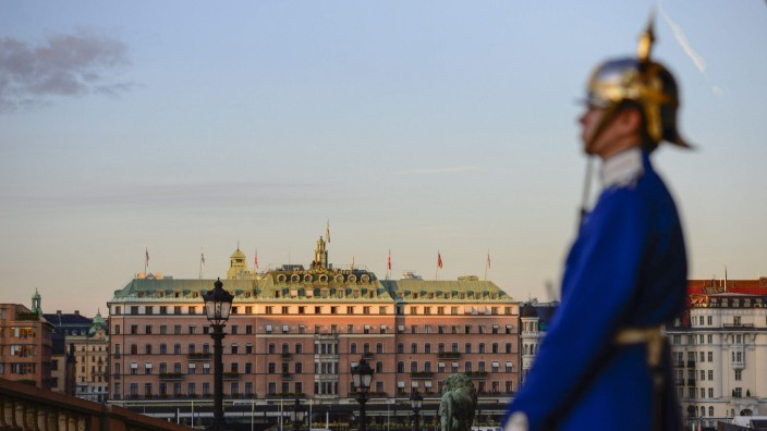 A palace guard stands in front of the Royal Palace while the sun sets over the Grand Hotel in downtown Stockholm