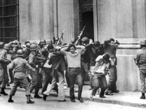 Members of the office of former Socialist President Allende are led out by soldiers outside La Moneda presidential palace in Santiago