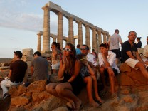 Tourists enjoy the sunset in the temple of Poseidon at cape Souni