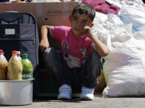 A Syrian boy sits beside his family's belongings as they wait for a vehicle to pick them up after entering Turkey from the Turkish Cilvegozu border gate, located opposite the Syrian commercial crossing point Bab al-Hawa, in Reyhanli, Hatay province