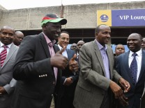 Kenya's Deputy President Ruto bids farewell to government officials as he leaves Jomo Kenyatta airport in Nairobi, on his way to the ICC at The Hague