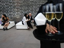 A bartender holds champagne for guests during a reception prior to a fashion show at the Ming Dynasty City Wall Relics Park in Beijing