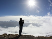 A man takes a picture near the peak of the Brienzer Rothorn mountain in front of the panorama of the Alps in the Bernese Oberland