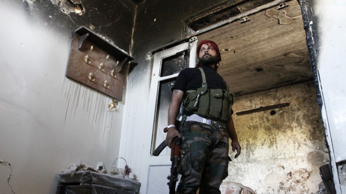A Free Syrian Army fighter holds his weapon as he stands guard inside a damaged house in Aleppo's Qastal al-Harami neighbourhood