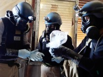 File photo of U.N. chemical weapons expert holding a plastic bag containing samples from one of the sites of an alleged chemical weapons attack in Ain Tarma