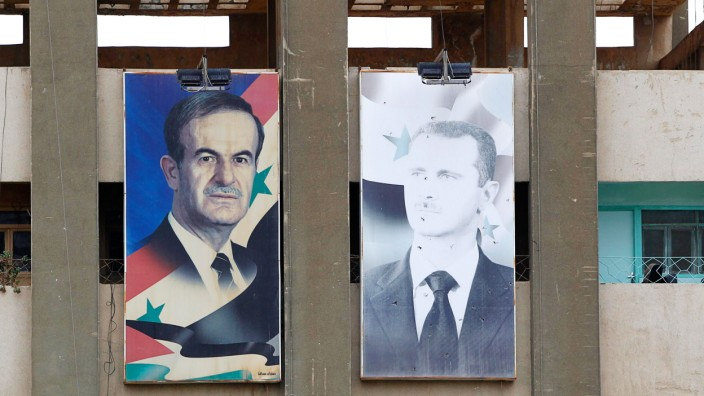 Pictures of Syria's President Assad and his father hang from a government building in Deraa