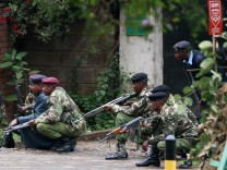 Police officers take position during the ongoing military operation at the Westgate Shopping Centre in Nairobi