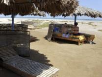 Touristen sitzen an einem leeren Strand in Hurghada am Roten Meer.