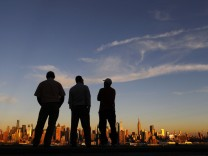 People watch the sun set over New York from a park in Weehawken, New Jersey
