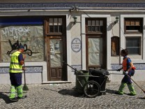 Cleaners sweep the street in front of a closed restaurant in Alges