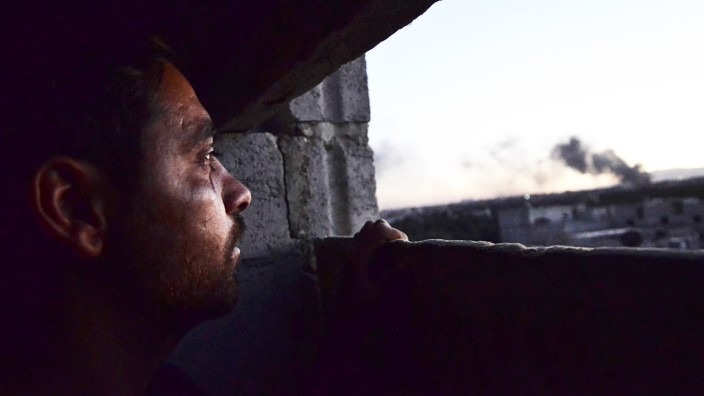 A man looks at smoke rising into the sky from what activists said was Free Syrian Army fighters destroying a tank that belonged to forces loyal to Syria's President Bashar al-Assad in the Qaboun area