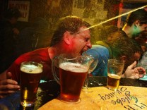 A party goer is splashed with water after winning a crab race at a pub called the 'Friend in Hand' in central Sydney
