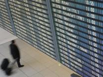 Passagier unter der Anzeigetafel auf dem Franz-Josef-Strauss Airport in München