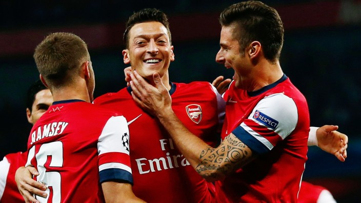 Arsenal's Ozil celebrates with teammate Giroud after scoring a goal against Napoli during their Champions League soccer match at the Emirates stadium in London