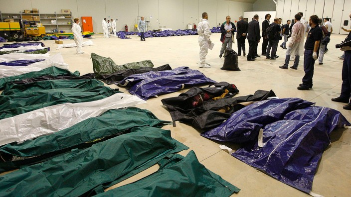 Body bags containing African migrants, who drowned trying to reach Italian shores, lie in a hangar of the Lampedusa airport