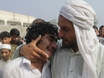 An Afghan man cries over the dead body of his brother, who according to the provincial government, was killed in a NATO air strike, on the outskirts of Jalalabad province