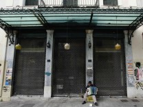 A street musician plays accordion in front of a closed shop in central Athens