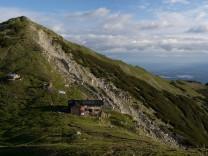om Krottenkopf ist die Hütte mit dem Oberen Risskopf (2049 m) im Hintergrund zu sehen. Bei klarem Wetter reicht der Blick bis weit ins Voralpenland.