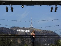A woman talks on her cellular phone in front of the Hollywood sign prior to the 84th Academy Awards in Hollywood, California