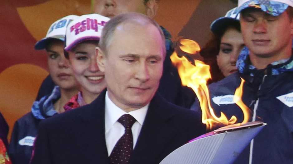 Russian President Putin holds a lighted Olympic torch during a ceremony to mark the start of the Sochi 2014 Winter Olympic torch relay in Moscow