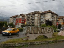 A car drives past a town sign at a road intersection in Aninoasa, west of Bucharest