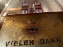 Model of Limburg cathedral sits on top of a donation box reading 'Thank you' inside the cathedral in Limburg