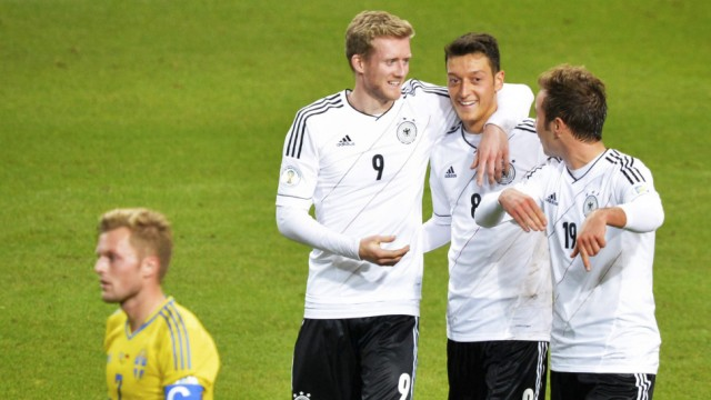 Germany's Schuerrle celebrates his goal against Sweden with teammates Ozil and Goetze behind Sweden's Larsson during their 2014 World Cup qualifying soccer match in Stockholm