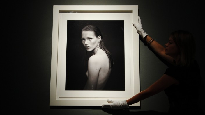 A worker poses with 'Kate Moss, for Calvin Klein Obsession campaign 1993' by photographer Mario Sorrenti, at Christie's auction house in London