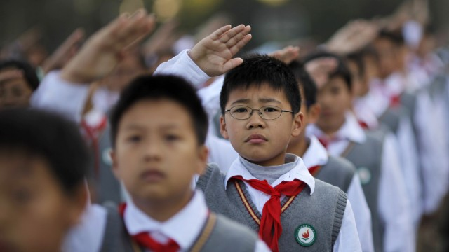 Young Pioneers salute during the weekly flag-raising ceremony at the East Experimental School in Shanghai